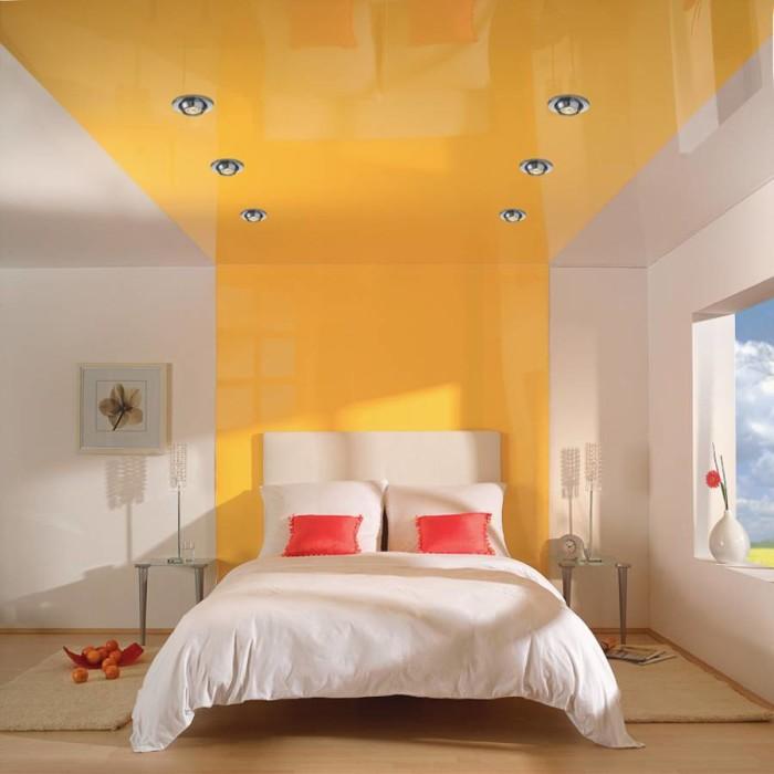 Глянец делает комнату просторнее за счет преломления света. Яркий желтый эффектно выглядит на белом фоне стен. Обратите внимание на зонирование спальни, выполненное при помощи данной конструкции