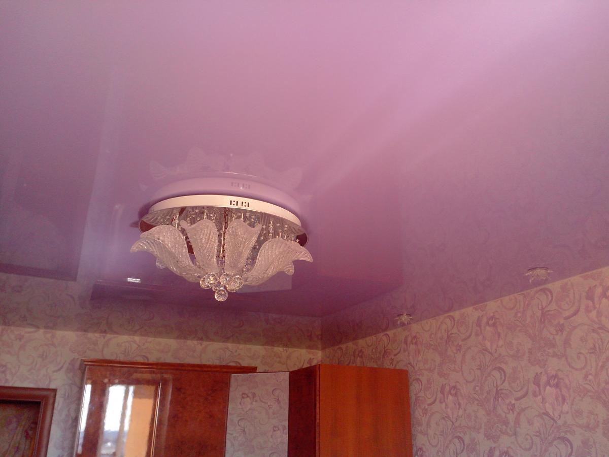Сатиновый натяжной потолок розового цвета с люстрой для зала