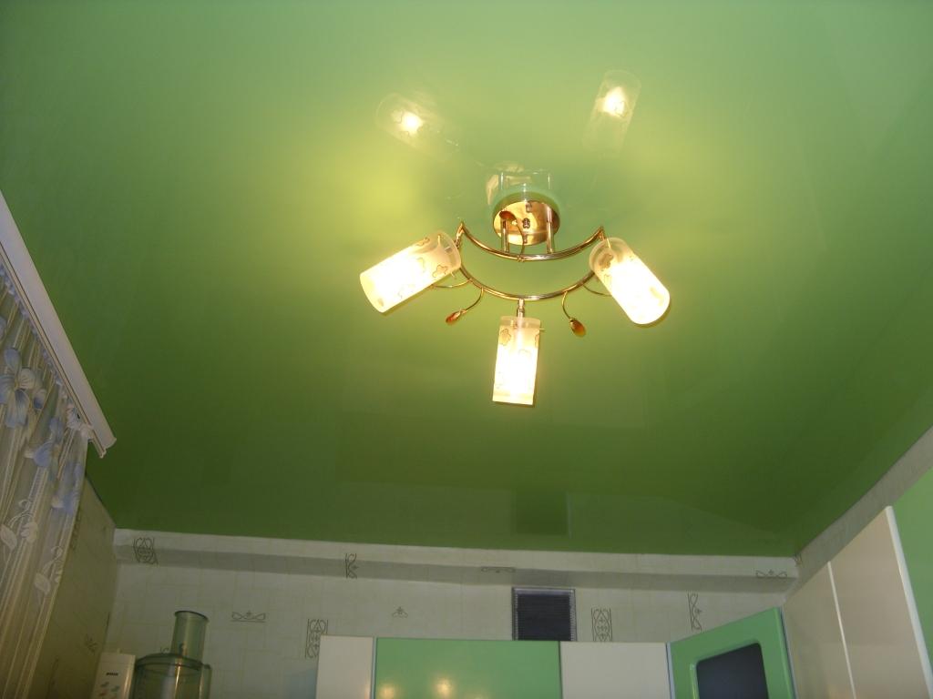 Сатиновый натяжной потолок зеленого цвета с люстрой на кухню