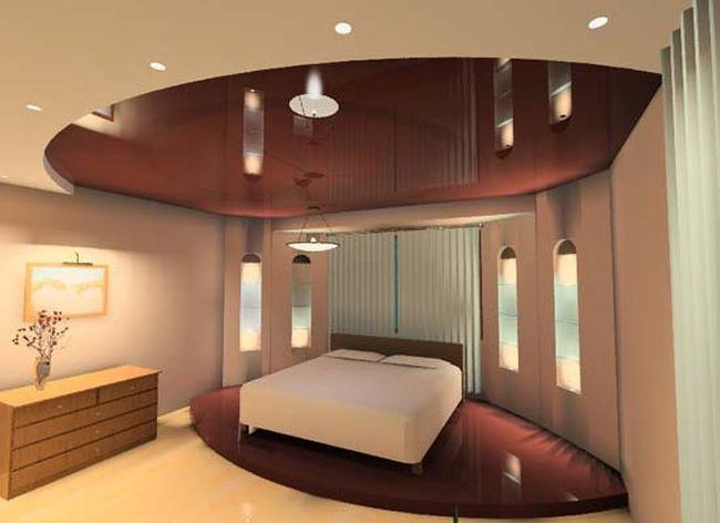 Потолочная натяжная конструкция находит отражение на полу спальной комнаты. Во всех смыслах. Занятная идея 'отражения' дизайна пола и потолка — выступающая конструкция подиума дополняет форму и вид первого уровня многоуровневого потолка